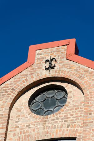 Rose window and a cast iron fixture of a brick factory house on polarised deep blue sky.
