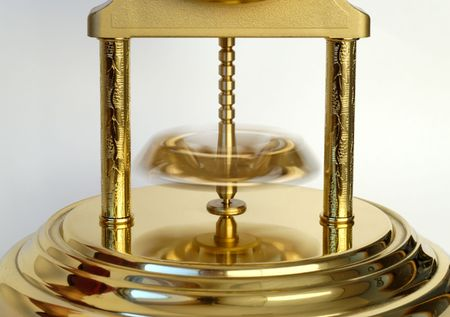 Rotating pendulum of a golden-coloured clock. Stock Photo - 3834649