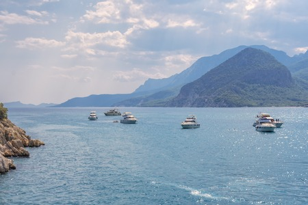pleasure boats at anchorage in the Gulf of the Mediterranean, against the backdrop of mountains covered with green vegetation and the sky covered with clouds.