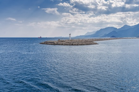 lighthouse on an artificial mound of stones at the entrance to the marina, a bay of parking ships and yachts, against the background of the sea, mountains, ships 免版税图像