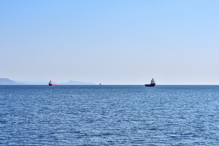 three ships intended for the transport of containers at anchorage in the sea, against the background of the mountainous coast and open sea