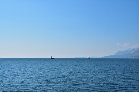 Two ships for transporting containers at anchorage in the sea, against the backdrop of the coastline, mountains, blue sky and small clouds