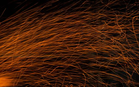 sparks of an open campfire scattering when a gust of wind Foto de archivo