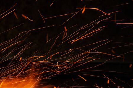 sparks of an open campfire scattering when a gust