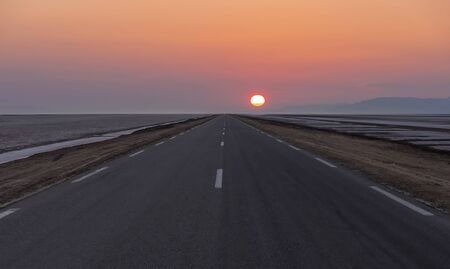 in asphalt road with road markings that goes into the distance among the desert to meet the morning rising sun.
