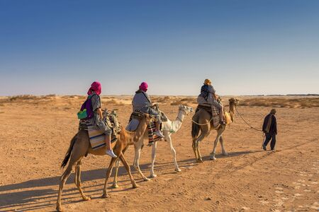 three people in Berber national robes on camel guided camels