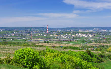 oil refinery, pipes, burning torch, crackers, hulls, storage tanks for petroleum products, against the backdrop of green vegetation and the city in the background Imagens