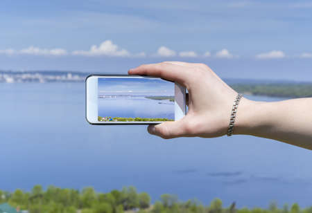 A photo of a male hand holding a smartphone with a surrounding landscape on the screen background surrounding the screen of the smartphone is blurred Banque d'images