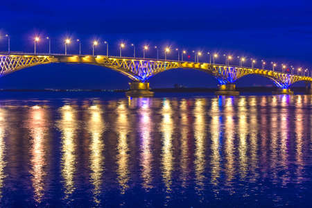 an automobile bridge across the Volga River at night, illuminated by the light of lanterns, the light of which is reflected in the river, Saratov, Russia