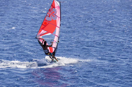 the windsurfer on the board under sail moves at a speed along the surface of the sea, against the background of waves and shoreline, windsurfing in the Red Sea