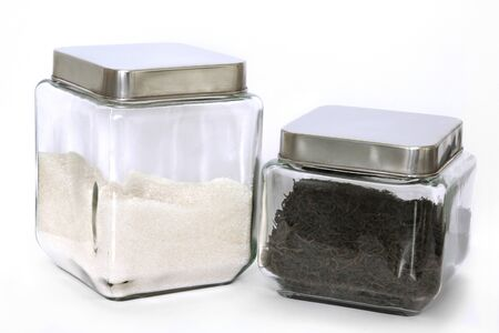 Two square glass jars with tea and sugar insade photo