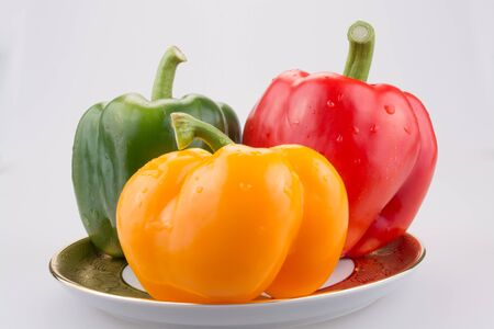 sweet peppers: Sweet peppers  isolated on white background in chinaware plate.