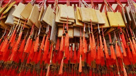wish: Small wooden plates to write your wishes on hanging in a Shrine in Suphunbui, Thailand. Stock Photo