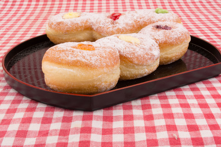 red stripe: Donuts buns in a plate on red stripe table cloth.