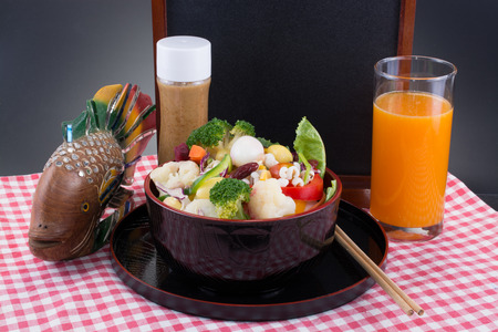 Vegetable salad with oriental sesame salad dressing with a glass of orange juice and a small black board background.