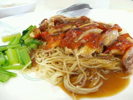 Roast duck noodle on white plate with gravy.