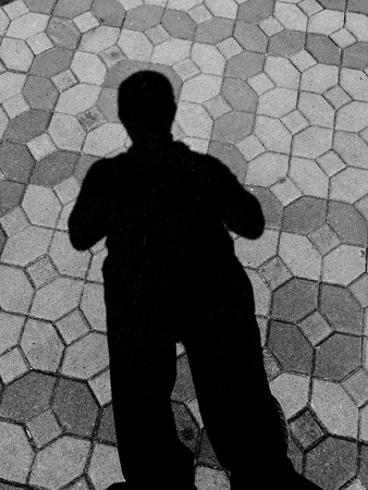 Dark shadow of a man using mobile phone on pedestrian bricks walkway background. Stock Photo