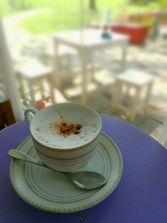 A latte coffee cup on purple table with blurry background.