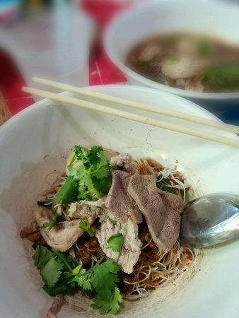 Pork noodles in white bowl with blurry background. Stock Photo