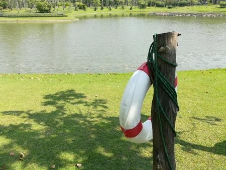 Doughnut shape lifebouy hanging on a post near a big pond. Stock Photo