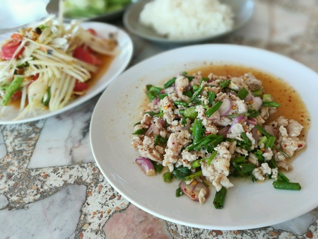 Minced pork salad served with sticky rice and papaya salad together with fresh vegetables side you.