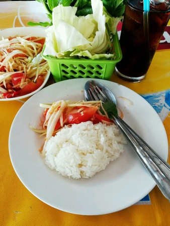 Papaya salad with sticky rice and vegetables side dish. Stock Photo