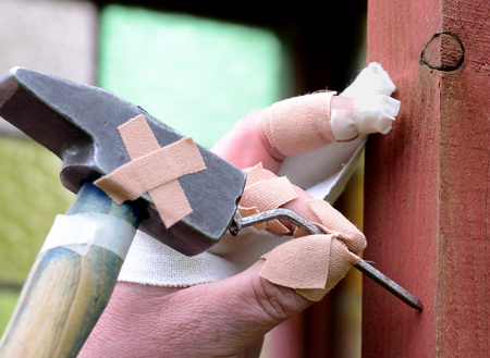 slovenly: Ten thumbs, heavily injured homeworker tries to hammer a bent nail in a wall.