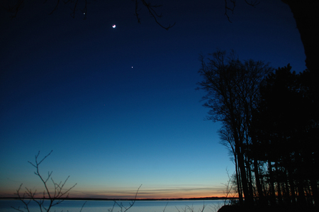 Conjunction between (left to right) Jupiter, Moon and Venus seen over the sea. Even Mercury can just barely be spotted right to the short gray contrail.