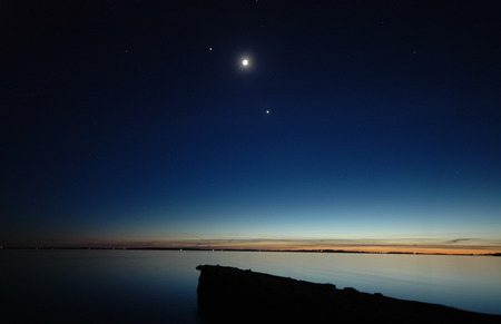 Conjunction between (left to right) Jupiter, Moon and Venus seen over a dead calm sea. Stock Photo - 85956535