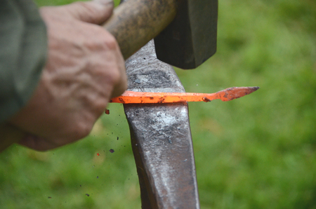 A piece of red hot iron being hammered on a vintage anvil.