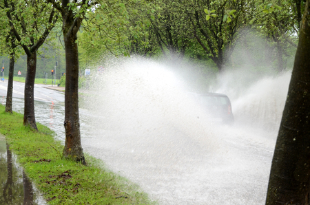 A car hidden in a large splash drives on a road that i flooded because of severe rainfall and bad kept drains.