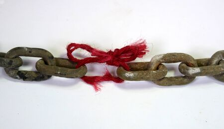 The weakest link; a massive chain where one link is replaced with a piece of red thread with frays.