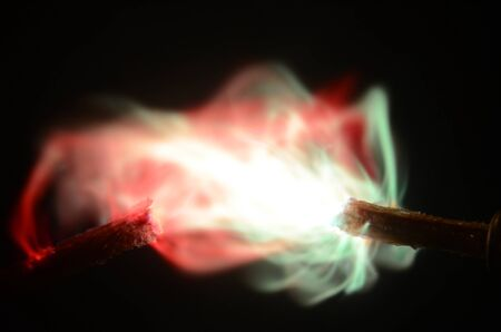 Colored sparks mainly with red and green nuances seen between two impregnated electrodes on a dark background