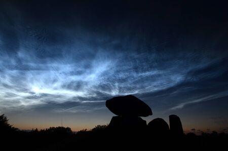 Paisaje nocturno con nubes noctiliucent azul acero con la silueta de un túmulo redondo en primer plano.