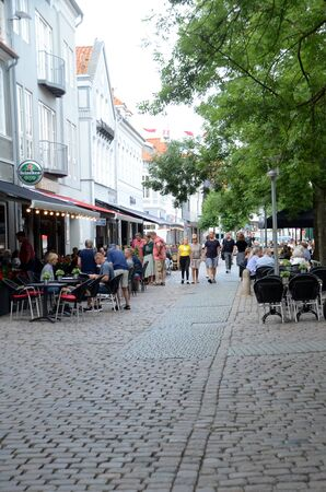 Sonderborg, Denmark - August 1, 2019: View up trough a lane with busy street cafes.