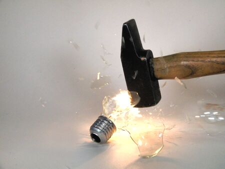 Closeup of an incandescent lamp being broken with a hammer, glass fragments fly around.