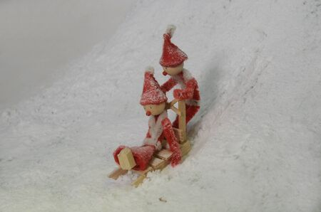 Two red pixies sledging downhill a snowey slope. Standard-Bild