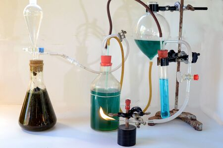 Small demonstration rig to make biogas, from left reactor with biomass, then two bottles with green water for pressure regulation, a test tube with blue water to prevent backfire in case of unclean gas, and finally the gas flame.