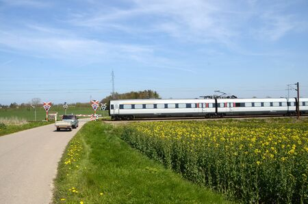 Ragebol, Denmark - May 1, 2017: An EMU train passes a level crossing with a waiting car south of town. Redactioneel