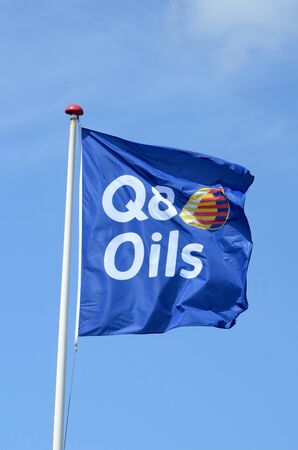 Sonderborg, Denmark - June 7, 2019: Blue Q8 Oils flag blow in the wind with a blue sky as background Redactioneel