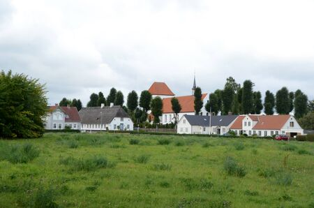 Spang, Denmark - August 30, 2013: View to the village Ulkebol, with church and old houses.