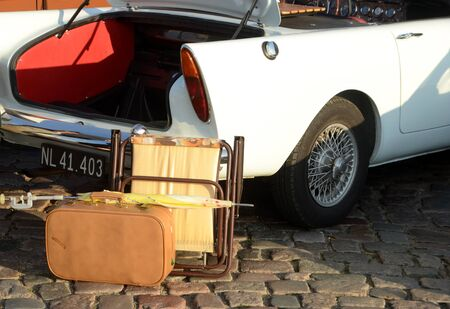 Sonderborg, Denmark -August 29, 2019: Vintage var with vintage luggage items beside the trunk.