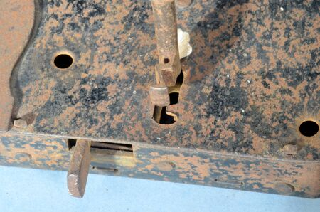 Vintage warded lock with attempted inserted key that does not fit.