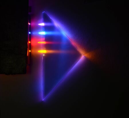 Four different light beams are refracted and mirrored internally a triangular 90 degrees prism on a dark background.