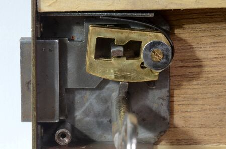 Closeup into a lock mechanism of a lever tumbler lock (front cover removed). This key fits, and the tumblers allow the opening of the lock. Stockfoto