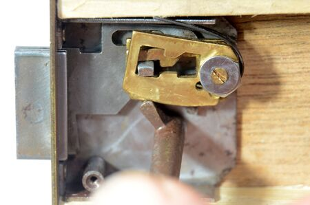 Closeup into a lock mechanism of a lever tumbler lock (front cover removed). The key does not fit, the front tumbler prevents an opening of the lockock.