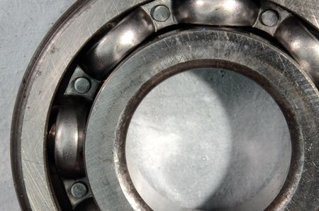 Macroview into a ball bearing where the balls can be seen arranged in their guide. The lubricant has been cleaned out for a better view.