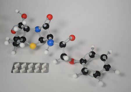 Molecule model of Penicillin V with sample. White is Hydrogen, black is Carbon, red is Oxygen, yellow is Sulphur and blue is Nitrogen.