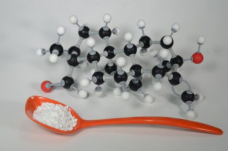 Molecule model of Stevia, the central element in a natural sweetener with sample in an orange spoon. White is Hydrogen, black is Carbon and red is Oxygen.