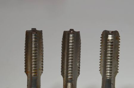 Closeup on M8 sized thread tap set with taper tap to the left, second tap in the middle, and bottoming tap to the right.